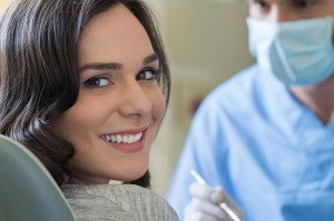 young female patient smiling as she receives dental care