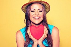 happy female patient smiling and holding a heart