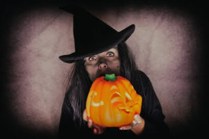 woman dressed up as a witch and holding a jack o'lantern