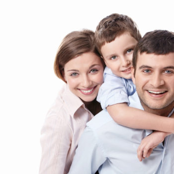 smiling parents with little boy on dad's shoulders