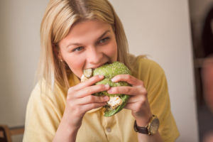 young woman eating a green sandwich