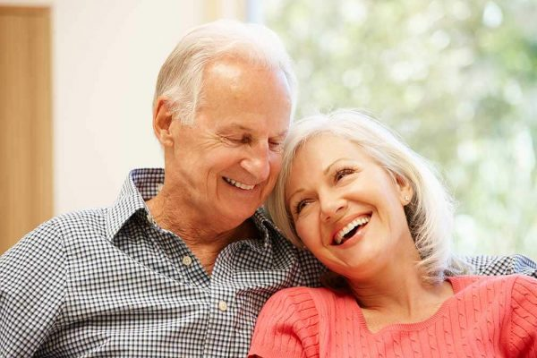 elderly couple smiling affectionately at each other
