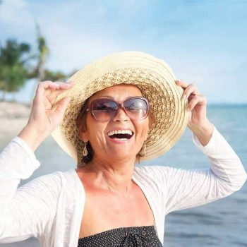 middle aged female patient smiling on the beach