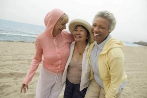 three middle-aged women walking on the beach and smiling