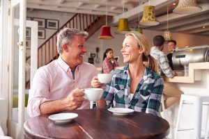 middle aged man and woman enjoying a date having coffee