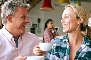 middle aged man and woman smiling at each other while drinking coffee
